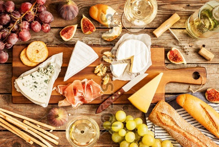 stock-photo-different-kinds-of-cheeses-wine-baguettes-fruits-and-snacks-on-rustic-wooden-table-from-above-334566584